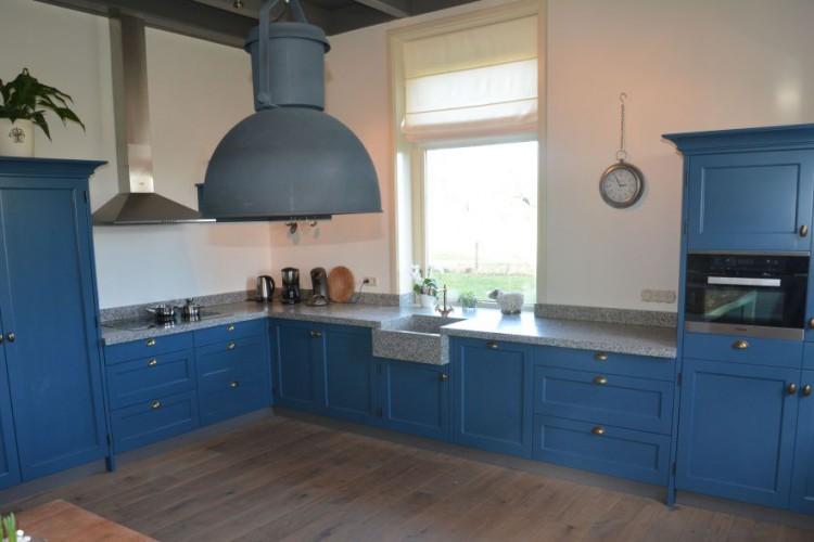 VRI interieur: donkerblauwe landelijke keuken met terrazzo blad